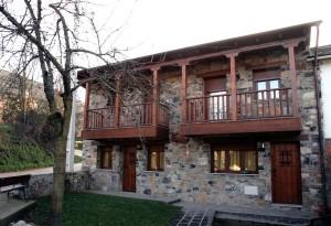 Fachada tradicional de piedra y balconada de madera